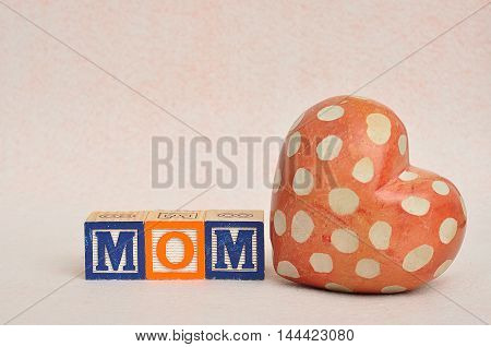 The word mom spelled with alphabet blocks with a heart