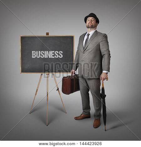 Business text on  blackboard with businessman holding umbrella and suitcase