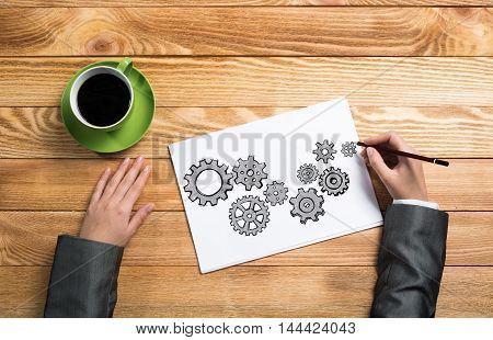 To view of businesswoman hands drawing on paper sheet gears mechanism