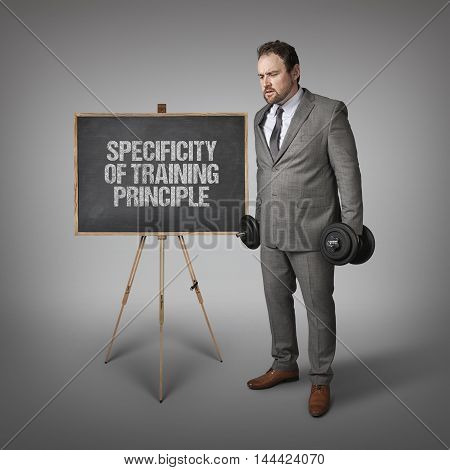 Specificity of Training Principle text on blackboard with businesssman holding weights