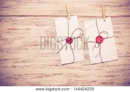 Envelopes with red wax seals hanging from twine on wooden background