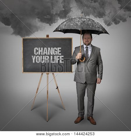 Change your life text on blackboard with businessman holding umbrella