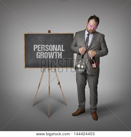Personal growth text on blackboard with businessman and key