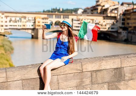Young female traveler taking selfie portrait with italian flag near the famous bridge in Florence