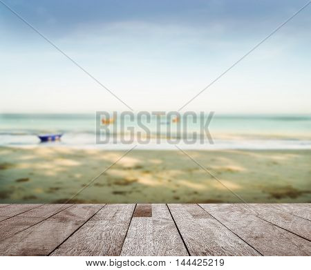 Wood floor top on blurred blue sea with sand beach and blue sky in morning light