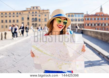 Young female traveler standing with paper map on the crowded bridge in Florence. Vacation in Italy