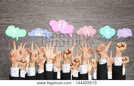 Many hands of businesspeople showing different gestures and internte clouds with icons.
