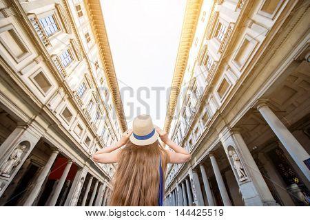 Young female traveler enjoying famous Uffizi museum in Florence. Back view