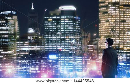 Elegant businessman in a suit looking out at night city