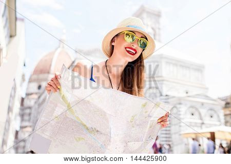 Young female traveler standing with paper map in front of Santa Maria del Fiore cathedral in Florence. Having great vacations in Italy