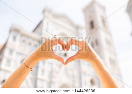 Hands in the form of heart with famous Santa Maria del Fiore cathedral on the backround in Florence