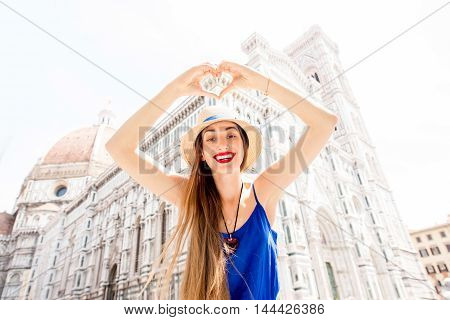 Young smiling woman in blue dress showing with hands heart shape in front of Santa Maria del Fiore cathedral in Florence. Promoting tourism in Italy