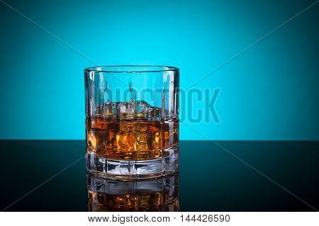 A glass of liquor in a studio setting.