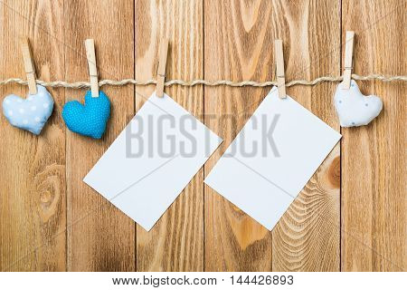 Blank sheet of paper hand made hearts pinned to twine on wooden background.