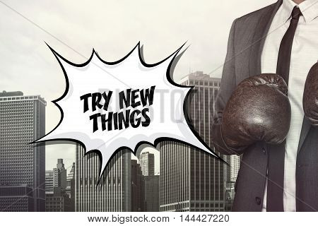 Try new things text on speech bubble with businessman wearing boxing gloves
