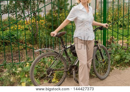 Young woman on a Bicycle standing on the road in the Park.