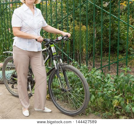 Middle-aged attractive blond woman on a Bicycle in the Park.