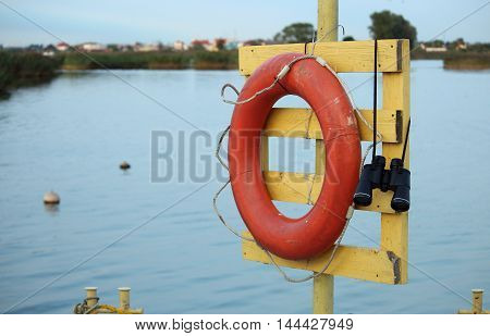 Lifebuoy and the field-glass on the mooring in port