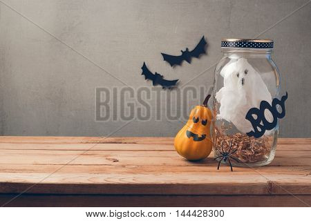 Halloween holiday decoration with ghost in jar and pumpkin with scary face on wooden table