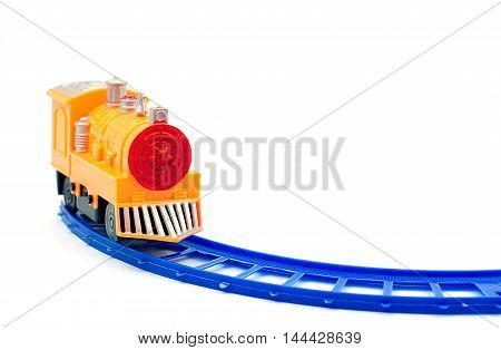 Yellow plastic train toy on blue railway isolated white background