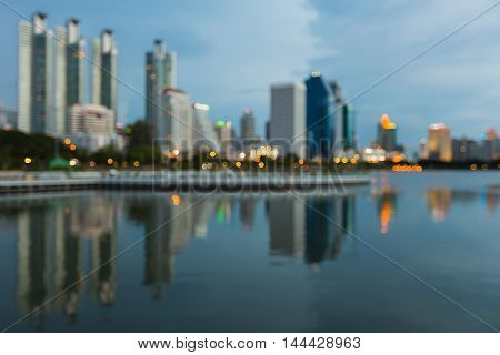 Blurred bokeh lights night view, city building and water reflection at twilight