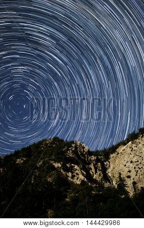 startrails on a clear night in the mountains with waterfall