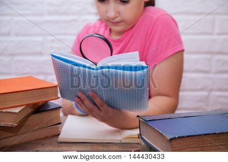 Girl looking through a magnifying glass in the diary