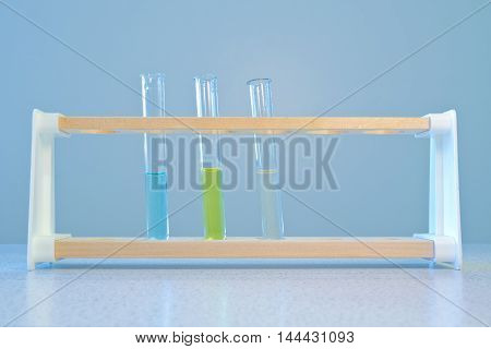 Three test tubes (one containing copper sulphate solution, one iron (III) chloride and one, iron (II) sulphate) standing in a wooden test tube rack.
