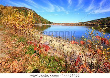Autumn colors along calm lake shoreline at Devil's Lake State Park, Wisconsin
