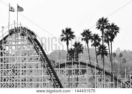 Santa Cruz, California, August 22, 2016 - the Big Dipper Roller-Coaster and Palm Trees, in black and white, mid-afternoon, Santa Cruz Beach Boardwalk Amusement Park
