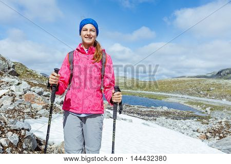 Best Norway hike. Beautiful girl with hiking equipment in the mountains