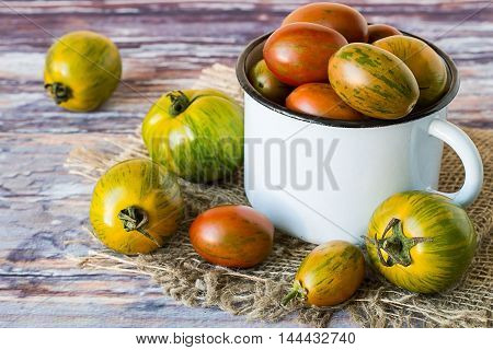 Freshly picked tomatoes in a white metallic mug and on the sackcloth on the old wooden table. Selective focus.