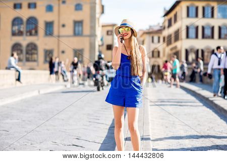 Young female traveler using mobile phone during the weekend in Florence