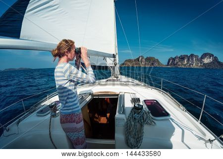 Lady sailor standing on the yacht and watching to the binoculars at sunny day