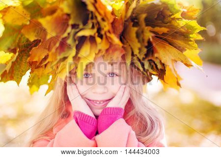 little girl in a crown from autumn leaves on a head