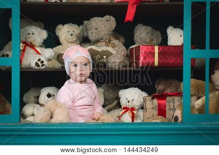 The little girl sits on a shelf storefront teddy bears