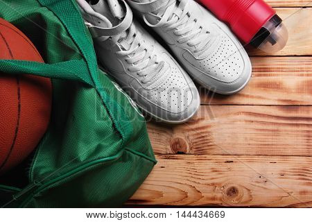 High white sneakers , Sport bag for basketball, Basketball ball inside the bag, sport bottle with water near. Concept basketball training.Top view. free space.Selective focus ball defocused