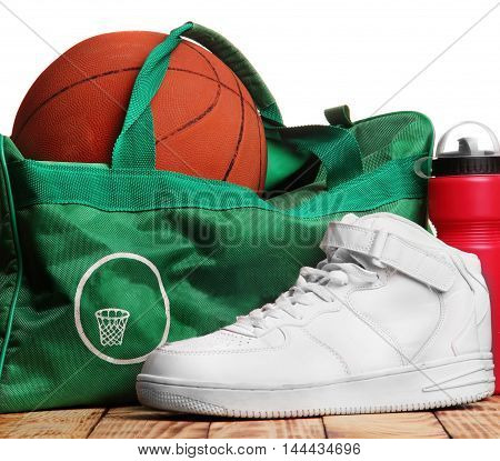 High white sneakers , Sport bag for basketball, Basketball ball inside the bag, sport bottle with water near.Top of photo white background down wooden background.Background.Concept basketball training