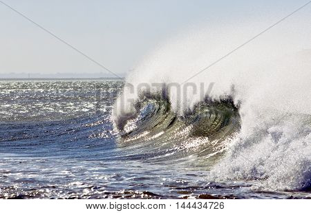 strong wing blowing causing sea spray on a large breaking wave