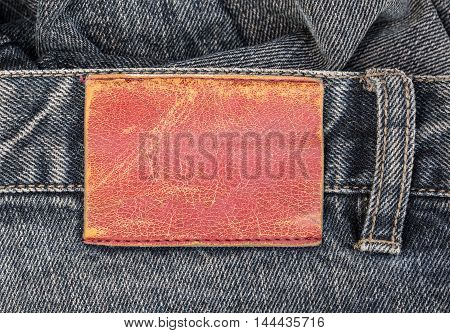 blank leather label on blue jeans background