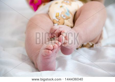 baby in modern eco stacks of cloth diapers and replacement bushings selective focus close-up bright background little cute foot kid the concept of health. hygiene of the child. reusable diapers