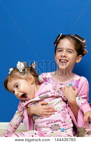 Two silly sisters sit in hair curlers and pajamas. The older sister holds her younger sibling from behind while laughing the smaller girl pretends to try to get away.