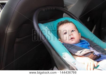 Portrait of toddler boy in car seat. Little smiling baby child fastened with seat belt portrait of adorable happy baby boy sitting in the car seat. concept in safety in the car.