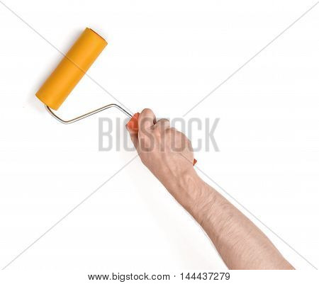 Close-up view of a man's hand with a paint roller, isolated on white background. Wall painting. Interior decorating. Building and trimming.
