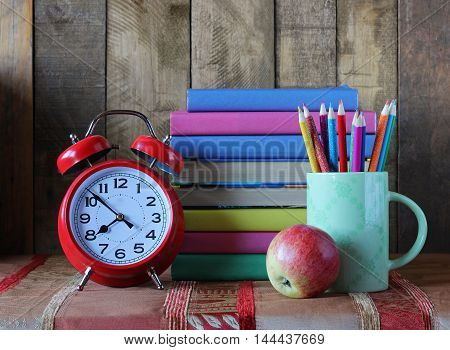 Alarm clock pencils and a stack of books. Back to school. Still life with books.