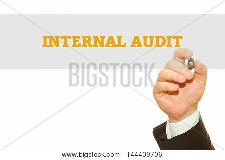 Businessman hand writing Internal Audit on a transparent wipe board.