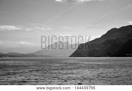 A beautiful view of a lake between several mountains, in the Alps