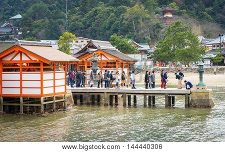 Hiroshima, Japan - March 16, 2016: Miyajima on March 16, 2016. Many tourists are standing in line for taking photo of Miyajima Torii.