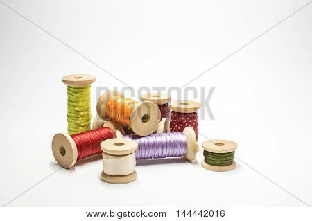 Satin ribbons on wooden spools on white