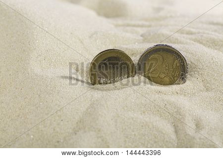 Euro coins close up in nice clean sand.